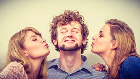 Two pretty young women kissing handsome man. Royalty Free Stock Photography