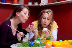 Two pretty young women painted eggs Royalty Free Stock Image