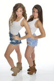 Two pretty young women pose in country western outfits Royalty Free Stock Images