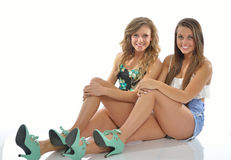 Two pretty young women pose in country western outfits Stock Photo