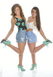 Two pretty young women pose in country western outfits Stock Photos