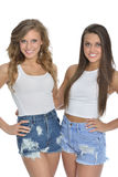 Two pretty young women pose in white tanks and denim Royalty Free Stock Images