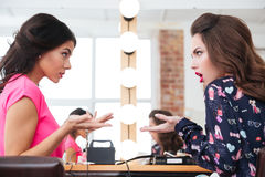 Two pretty young women sitting and arguing Stock Photos