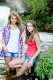 Two teen girls and summer outdoors near waterfall Royalty Free Stock Image