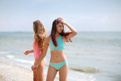 Two pretty young women wearing swimwears walking on a natural background. Girlfriends relaxing on a sea beach. A photo of two beautiful and sexy girls in Royalty Free Stock Photos