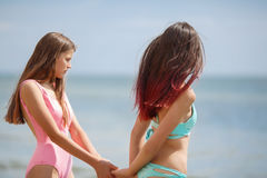 Two pretty young women wearing swimwears walking on a natural background. Girlfriends relaxing on a sea beach. A photo of two beautiful and sexy girls in Stock Photos