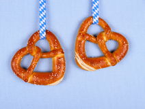 Two pretzel in heart shape on blue background Stock Photos
