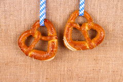 Two pretzel in heart shape on jute background Stock Photography