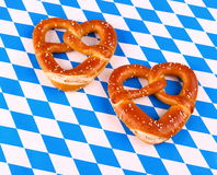 Two pretzel in heart shape on white blue background Stock Images