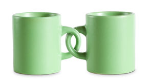 Two for the price of one cups. Two for the price of one cups, concept on green coffe cops with interlocked handles Stock Photography