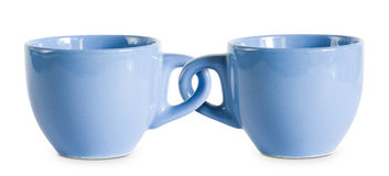 Two for the price of one cups. Two for the price of one cups, concept on blue coffe cops with interlocked handles Royalty Free Stock Photography