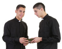 Two priests passing a bible Stock Images