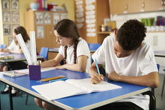 Two primary school pupils working at their desks in class Royalty Free Stock Photo