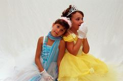 Two Princesses. Two dancer princesses with white gloves and tiaras having fun as little girls royalty free stock photo