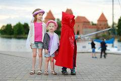 Two princesses and a knight having fun outdoors Stock Image