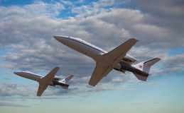 Two private jets flying Stock Photos