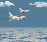 Two private jets flying over the ocean royalty free stock photo