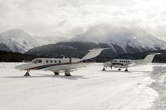 Two private jets in the snow covered airport of St Moritz in the alps switzerland in winter Royalty Free Stock Images