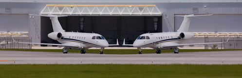 Two private planes in front of a hangar. At the airport Stock Photography