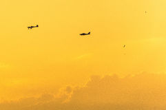 Two private planes in a yellowish orange sky. Two private planes seen one behind the other are seen flying across a yellowish-orange sky as a result of the Royalty Free Stock Photo