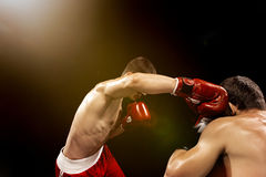 Two professional boxer boxing on black background,. Two professional boxer boxing on black studio background stock image