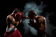 Two professional boxer boxing on black smoky background,. Two professional boxer boxing on black smoky studio background stock images
