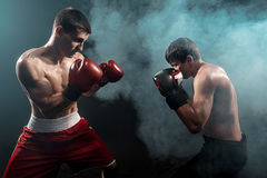Two professional boxer boxing on black smoky background, Stock Image