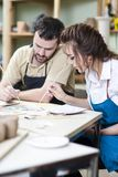 Two Professional Ceramists Glazing and Painting Ceramic Clay Tiles. In Workshop Together. Paint Pallet on aForeground. Vertical image Orientation Stock Photography