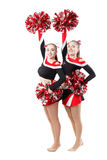 Two professional cheerleaders posing at studio. Hands raised up. Stock Photos
