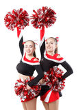 Two professional cheerleaders posing at studio. Hands raised up. Royalty Free Stock Image