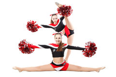 Two professional cheerleaders posing at studio. Side split and vertical split. Royalty Free Stock Images