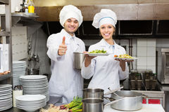 Two professional cookes working. Two positive professional cookes working at restaurant kitchen royalty free stock photography