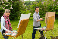 Two professional creative pensive painters painting in a garden. Two professional creative pensive painters working  on a trestle and easel painting with oils Royalty Free Stock Image