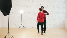 Two professional dancers - female and male is dancing together in studio. Close up stock video footage