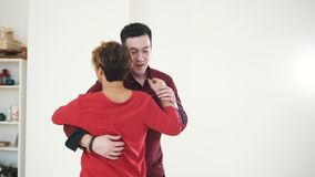 Two professional dancers in red shirts - female and male is dancing together in studio. Close up stock footage