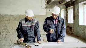 Two professional engineers working together at the desk with building documentation on construction area. Two professional engineers dressed in uniform and stock video footage