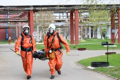 Two professional firefighter firefighters in orange protective fireproof suits, white helmets and gas masks carry the injured pers royalty free stock photo