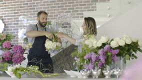 Two professional florists making large bouquet for client at flower shop. Couple of floral artists, florists working at flower shop. Floristry, handmade and stock video