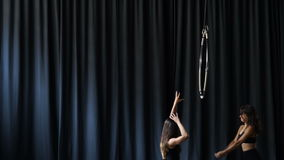 Two professional gymnasts are gesturing hands at the dark curtain background stock video footage
