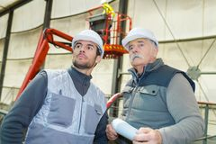 Two professional labours working on machine. Men stock photo