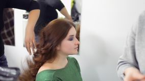 Two professional masters prepares actress to performance in theatre. Makeup artist draws woman`s eyes with pencil. Hairdresser makes the hairstyle for actress stock video footage