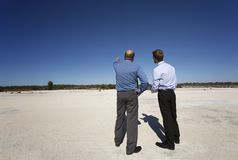 Business Opportunity Knocks. Two professional men discussing future plans for unused land, optimistic despite the desolate environment Stock Images