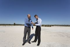 Business Opportunity Knocks. Two professional men discussing future plans for unused land, optimistic despite the desolate environment Royalty Free Stock Photo