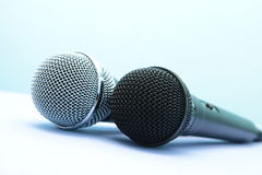 Two professional microphones on a light background. Two professional microphones for musical executors on a light background Royalty Free Stock Image
