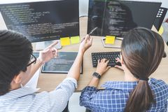 Two professional programmers cooperating at Developing programming and website working in a software develop company office, writ. Ing codes and typing data code royalty free stock photo