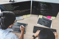 Two professional programmers cooperating at Developing programming and website working in a software develop company office, writ. Ing codes and typing data code stock photography