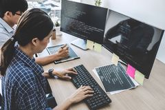 Two professional programmers cooperating at Developing programming and website working in a software develop company office, writ. Ing codes and typing data code stock photos