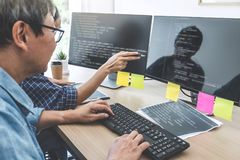 Two professional programmers cooperating at Developing programming and website working in a software develop company office,. Writing codes and typing data code stock photography