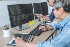 Two professional programmers cooperating at Developing programming and website working in a software develop company office,. Writing codes and typing data code royalty free stock images