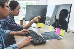 Two professional programmers cooperating at Developing programming and website working in a software develop company office,. Writing codes and typing data code royalty free stock photo